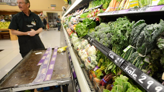 Michael LeRoi works in the produce department on Tuesday, April 28, 2015, during the Haggen grocery store opening in Keizer.