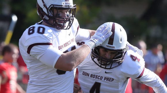 In this 2014 photo, Jimmy Schulz of Don Bosco celebrates a field goal by Leo Vagias of Don Bosco.