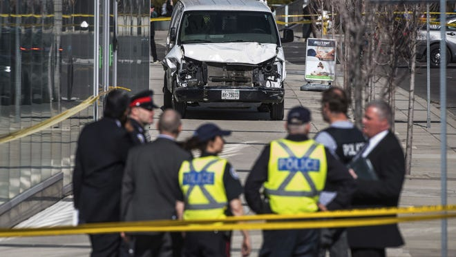 Police are seen near a damaged van after a van mounted a sidewalk crashing into pedestrians in Toronto on April 23, 2018.