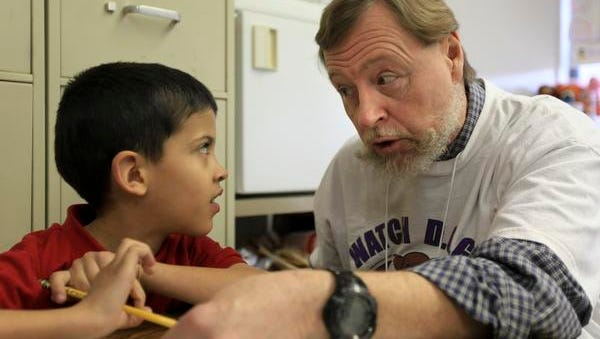 Greg Whittington, right, works with Hawthorne Elementary second-grader Christopher Hall.