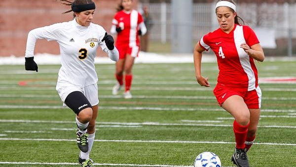 North Rockland's Amber Alfonzo, right, brings the ball upfield during the Class AA state championship game Sunday at SUNY Cortland. Massapequa defeated North Rockland 1-0.