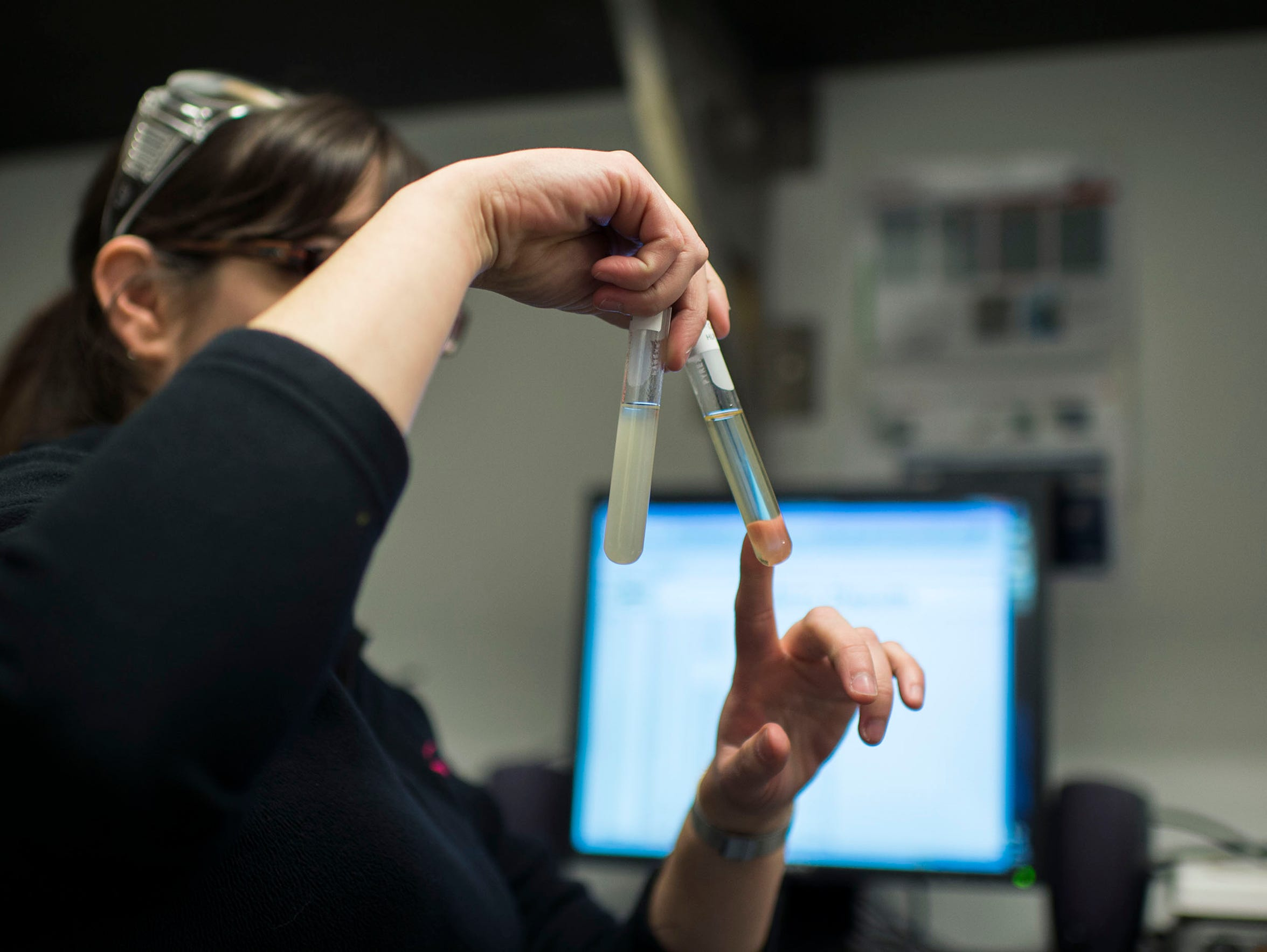 Quality technician Aimee Garlit checks on test tubes