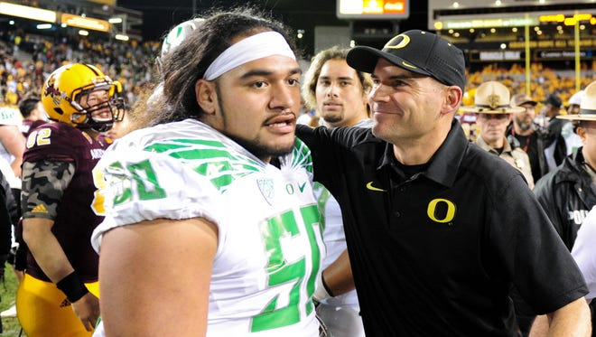 Coach Mark Helfrich celebrates with defensive lineman Austin Maloata (50) after Oregon beat Arizona State 61-55 in triple overtime Oct. 29, 2015.