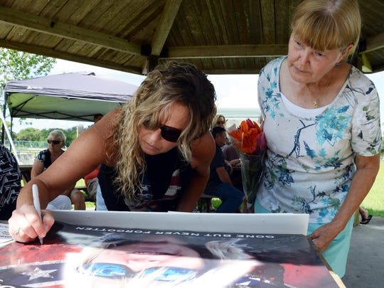 Debbie Rogge (right), mother of Brandy Hall, watches as Cher Rider signs a photo of Brandy in Malabar Community Park Saturday. Friends and family gathered in the park for a celebration of her Brandy's life. She disappeared after leaving work 10 years ago.
