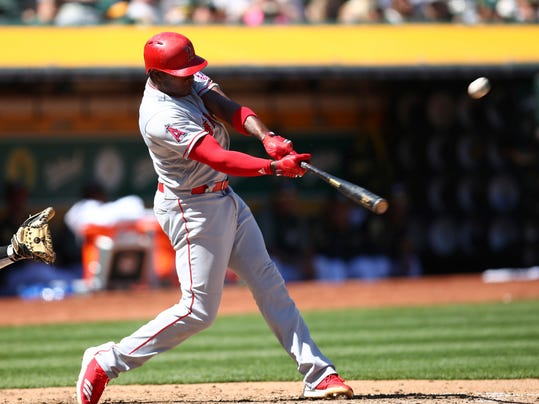 Los Angeles Angels' Justin Upton swings for an RBI sacrifice fly during the fifth inning of a baseball game against the Oakland Athletics on Sunday, April 1, 2018 in Oakland, Calif. (AP Photo/Ben Margot)