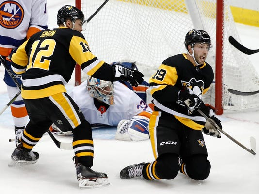 FILE - In this March 3, 2018, file photo, Pittsburgh Penguins' Derick Brassard (19) celebrates putting the puck behind New York Islanders goaltender Christopher Gibson (33) during the third period of an NHL hockey game in Pittsburgh. The Penguins won the 2009 Stanley Cup going with Sidney Crosby, Evgeni Malkin, Jordan Staal and Maxime Talbot down the middle and captured it the past two years with Crosby, Malkin, Nick Bonino and Matt Cullen. The free agent departures of Bonino and Cullen left a void that Pittsburgh filled by trading for Derick Brassard and Riley Sheahan to again look like a championship contender. (AP Photo/Gene J. Puskar, File)