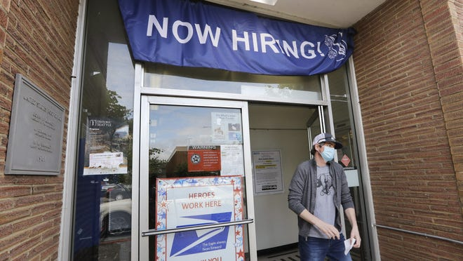 In this photo taken Thursday, June 4, 2020, a customer walks out of a U.S. Post Office branch and under a banner advertising a job opening, in Seattle.  The U.S. unemployment rate fell to 13.3% in May, and 2.5 million jobs were added þÄî a surprisingly positive reading in the midst of a recession that has paralyzed the economy and depressed the job market in the wake of the viral pandemic