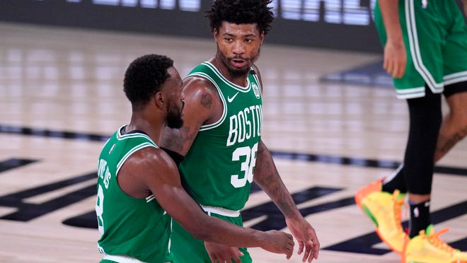 Boston Celtics' Kemba Walker, let, and Marcus Smart (36) talk on the court during the second half of an NBA conference final playoff basketball game against the Miami Heat on Saturday, Sept. 19, 2020, in Lake Buena Vista, Fla.