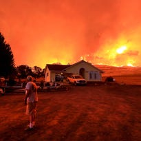 A wall of flames lurches over a ridge as a resident of Morgan Valley Road near Lower Lake, Calif., prepares to evacuate because of the Rocky Fire, Wednesday evening July 29, 2015.
