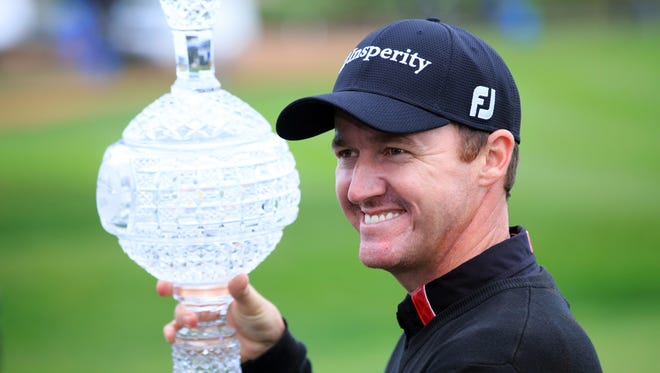 Jimmy Walker celebrates with the championship trophy after his victory during the final round of the AT&T Pebble Beach Pro-Am at Pebble Beach Golf Links.