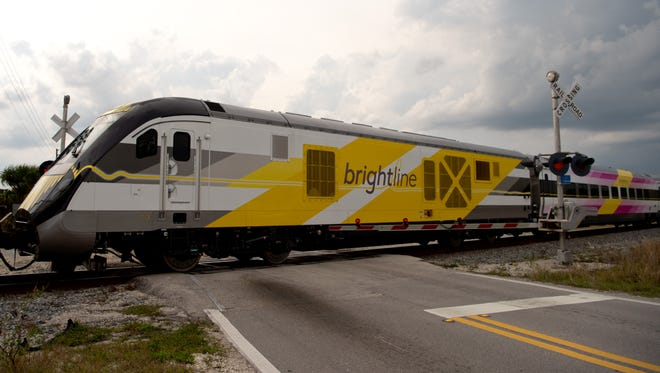 A Brightline passenger train, pulled by a Florida East Coast engine, moves south past the Walton Road crossing in Port St. Lucie.