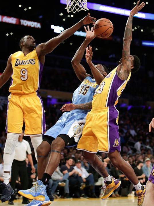 Denver Nuggets' Kenneth Faried, center, drives between Los Angeles Lakers' Luol Deng, left, and Lou Williams during the first half of an NBA basketball game, Tuesday, Jan. 31, 2017, in Los Angeles. (AP Photo/Jae C. Hong)