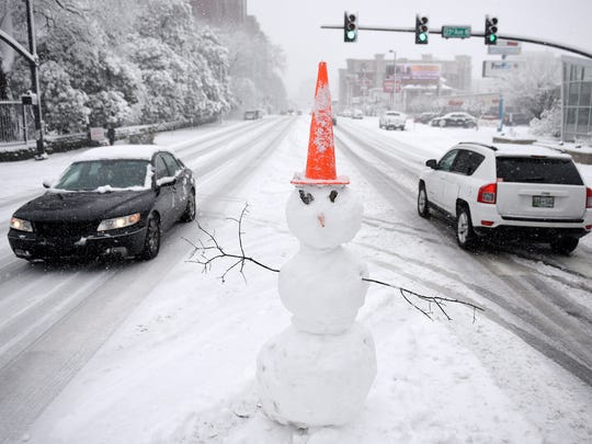 A snowman sits in the middle of West End Ave at 23rd Avenue North during a snowstorm in January of 2016, in Nashville.