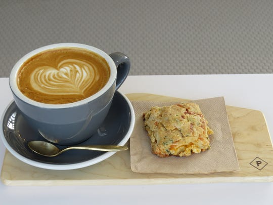 A specialty espresso drink called the Ventucky, left, and a savory scone are served on a home plate-shaped wooden board at Prospect Coffee Roasters in downtown Ventura.