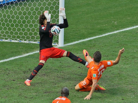 Mexico's goalkeeper Guillermo Ochoa makes a save after a shot by Netherlands' Klaas-Jan Huntelaar during the World Cup round of 16 soccer match between the Netherlands and Mexico at the Arena Castelao in Fortaleza, Brazil, Sunday, June 29, 2014. (AP Photo/Themba Hadebe)