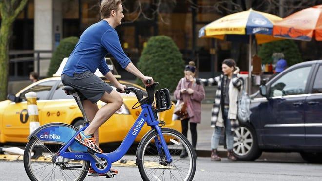 A man rides a rental bike through a downtown Manhattan street on Christmas Eve.