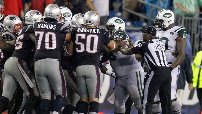 New England Patriots guard Logan Mankins (70) and defensive end Rob Ninkovich (50) fight with New York Jets guard Willie Colon (66) in the fourth quarter at Gillette Stadium.