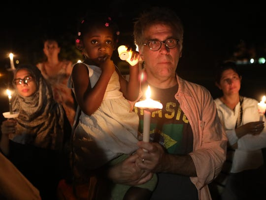 Mark Desiderio of Teaneck holds his adopted daughter, Olivia, 4, at the vigil Sunday night on the green in front of the Teaneck municipal building to protest the weekend's violence in Charlottesville, Virginia.