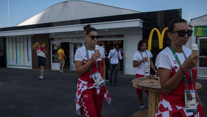 Members of Croatia's Olympic team eat ice cream outside of McDonalds as they walk in the athletes' village of the Rio 2016 Olympic Games on Aug. 1.