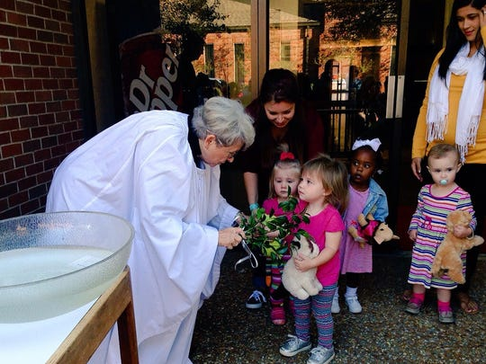 The Rev. Ella Breckenridge blesses a toy cat of Quinn Basco, a 2-year-old student at St. James Episcopal Day School, in a blessing of the animals Friday.