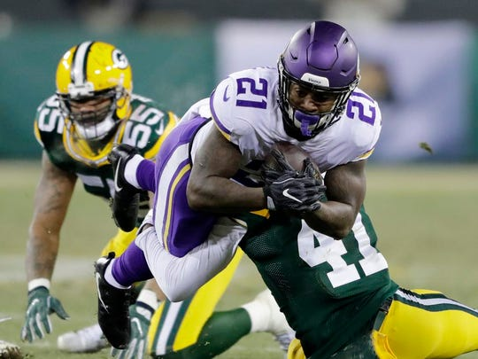 Minnesota Vikings running back Jerick McKinnon (21) dives for yards while being tackled by Green Bay Packers cornerback Lenzy Pipkins (41) at Lambeau Field on Saturday, December 23, 2017 in Green Bay, Wis.
