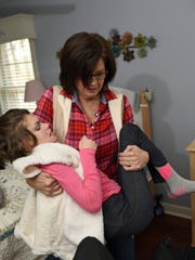 Karen Diller often lifts her daughter, Karly, 20, out of bed at their Chambersburg area home. Karly was born with a rare X-linked genetic disorder that causes seizures called CDKL 5 and is on a clinical trial of a drug that uses marijuana.
