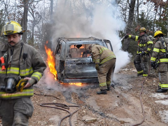 Mountain Home firefighters extinguish a 2013 Dodge Caravan on Skyline Drive Monday morning. The minivan is believed to be the third of a stolen car spree by Danny Wayne Bobbitt, who was later captured following a manhunt near Baxter Regional Medical Center.
