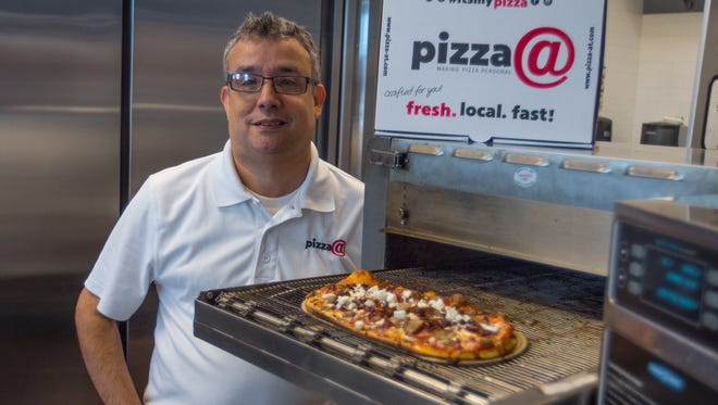 Stephen Weiss, owner of Pizza@Tituslanding shows off one of the restaurant's made-to-order personal pizzas.