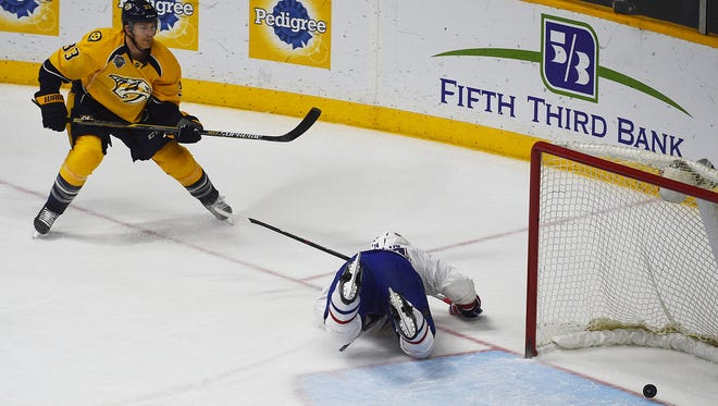 Predators center Colin Wilson (33) scores an empty net goal Alexei Emelin (74) of the Canadiens tries to stop the puck.