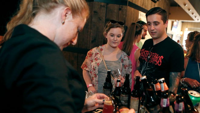 Taverna's Sami Reilly pours beers for Jenna and Greg Coumatos of Newark during the Downtown Newark Food and Brew Festival.