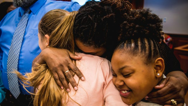 Christina Sanders embraces her newly adopted daughter Cayley, 12, and her biological daughter, Caitlyn, 9, after the Sanders family's adoption of Cayley and her five siblings was finalized in Hamilton County Probate Court on Thursday, April 27, 2017, in Cincinnati. The couple have five biological children and now have a total of 11 children.