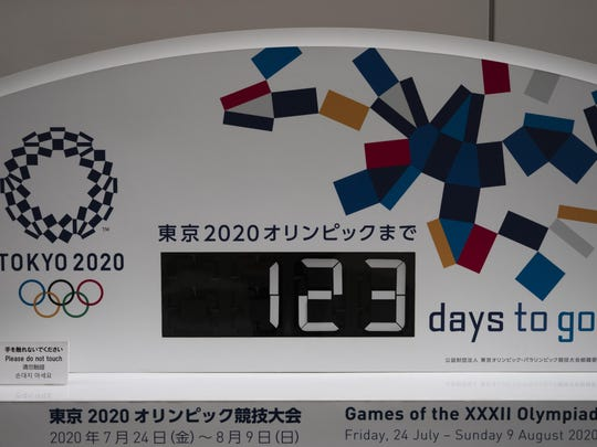 A countdown clock for the Tokyo 2020 Olympics is photographed in Tokyo, Monday, March 23, 2020. The IOC will take up to four weeks to consider postponing the Tokyo Olympics amid mounting criticism of its handling of the coronavirus crisis that now includes Canada saying it won't send a team to the games this year and the leader of track and field, the biggest sport at the games, also calling for a delay. (AP Photo/Jae C. Hong)