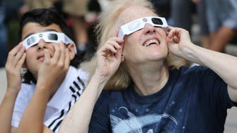 Eileen White and Ziad Souki, 12, watch the solar eclipse from the Johnson Public Library in Hackensack on Monday.