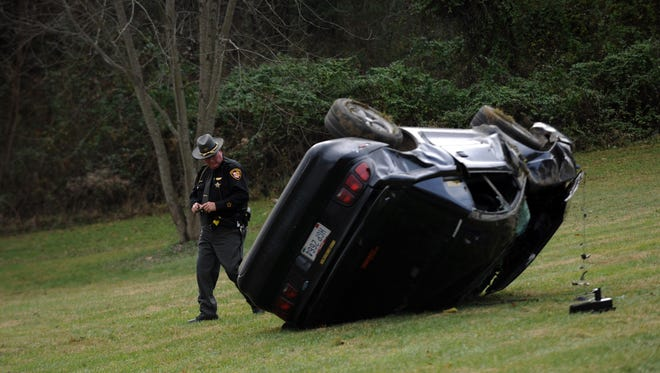 Fairfield County Sheriff's Dep. Mark Ratcliff walks around an overturned Ford Mustang Monday morning, Dec. 4, 2017, on Hamburg Road near Stoney Hill Road in Hocking Township. Ratcliff said the car, driven by Jacob Haydocy, 20, from Tarlton, went off the road and flipped while heading north on Hamburg Road while driving to avoid a delivery truck that had stopped to turn left on Stoney Hill Road. Haydocy was alert and conscience when he was transported to Fairfield Medical Center. It wasn't immediately clear if Haydocy crawled from the vehicle after it flipped or if was thrown free during the carsh.