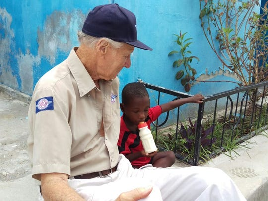 Remote Area Medical founder Stan Brock sits with a young boy in western Haiti, during Hurricane Matthew relief efforts.