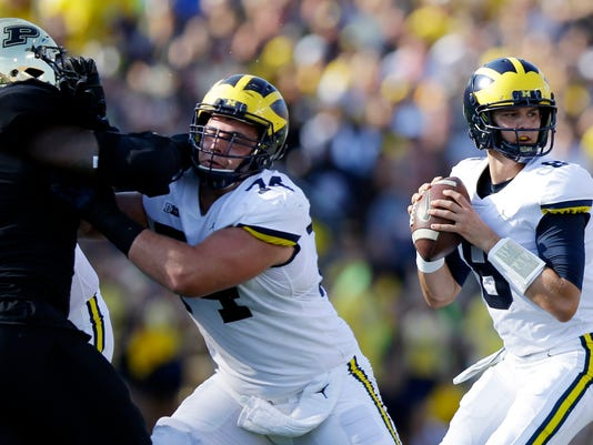 FILE - In this Saturday, Sept. 23, 2017, file photo, Michigan quarterback John O'Korn (8) looks to pass during the first half of an NCAA college football game against Purdue in West Lafayette, Ind.  Seventh-ranked Michigan has lost quarterback Wilton Speight for multiple weeks with an undisclosed injury. Coach Jim Harbaugh said Monday, Oct. 2, 2017, that John O'Korn will start Saturday night when the Wolverines play against Michigan State.(AP Photo/Michael Conroy, File)