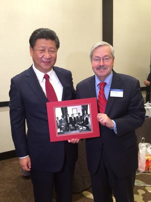 Chinese President Xi Jinping and Gov. Terry Branstad in 2015 display a 1985 photo that was taken when Xi was part of a Chinese delegation visiting the Iowa governor's office in Des Moines. Branstad was serving his first term as governor at the time.