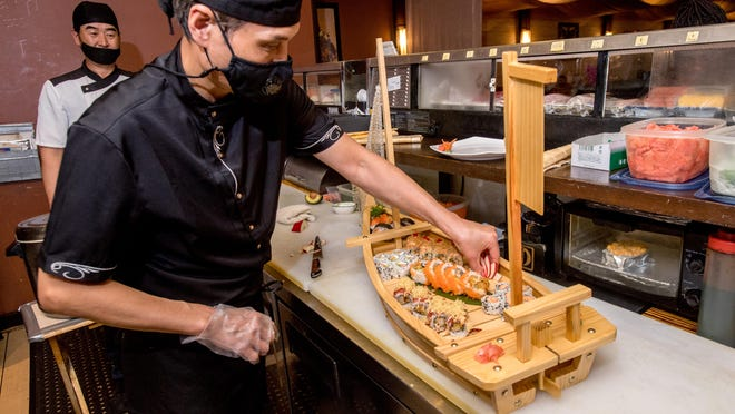 Sushigawa chef John Shin puts the finishing touches on a wooden boat full of sushi rolls at the popular restaurant, 2601 West Lake Avenue #A-2B, in Peoria.