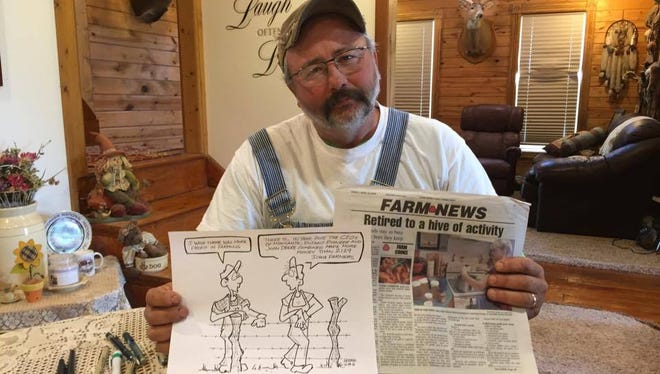 Rick Friday shows his editorial cartoon editorial cartoon that bemoaned Iowa farmers' dwindling profits. He says The Farm News terminated his employment after a company affiliated with one of three large corporations he portrayed in his cartoon complained.
