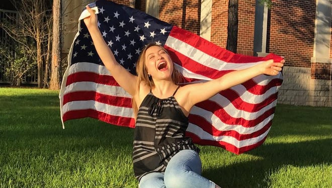 The smile says it all, Sara Nieto expresses her joy whilst proudly lifting the American flag.