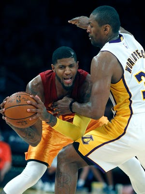 Indiana Pacers forward Paul George, left, gets fouled by Los Angeles Lakers forward Metta World Peace (37) during the second half of an NBA basketball game in Los Angeles, Sunday, Nov. 29, 2015. Indiana Pacers won 107-103. (AP Photo/Alex Gallardo)