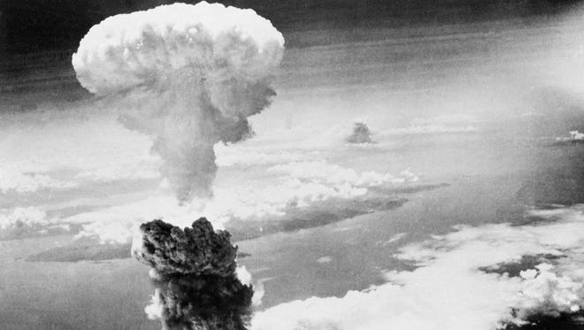 A giant column of smoke rises to form a mushroom cloud after the second nuclear bomb ever used in warfare explodes over the Japanese port and town of Nagasaki, on August 9, 1945.