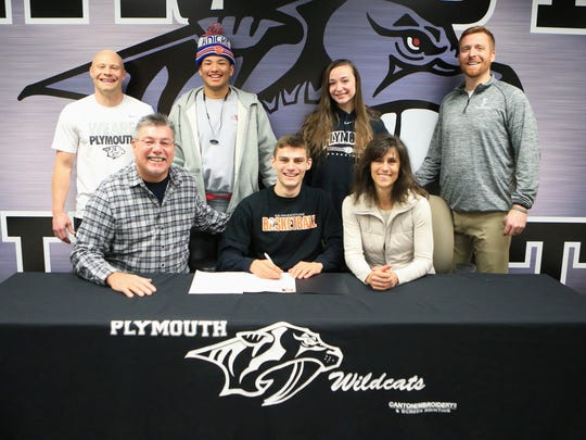 Plymouth senior boys basketball player Joey Robb, along with family members and coaches, celebrates signing with Kalamazoo College.