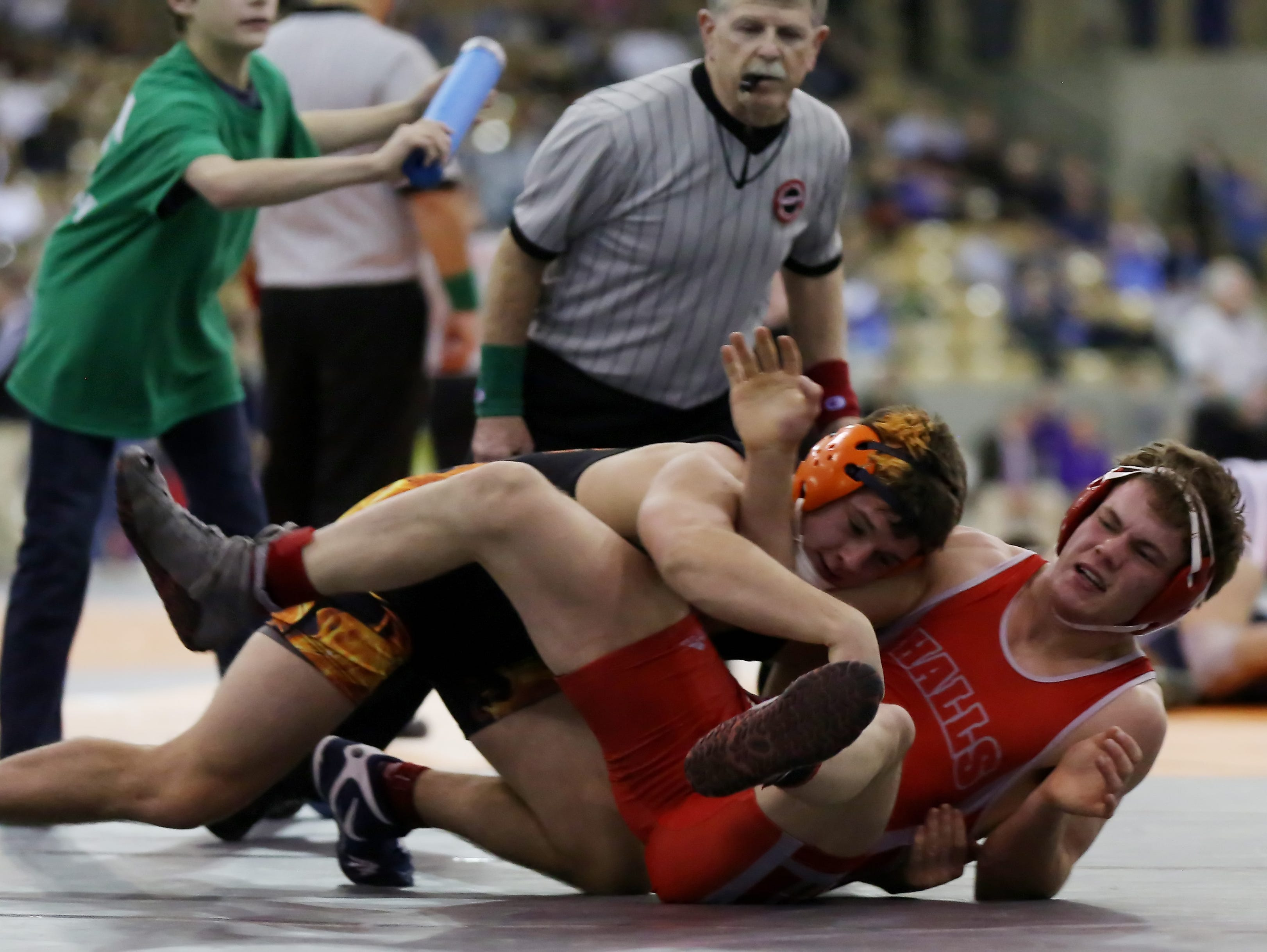 Matthew Sells of Blackman, left, in black and orange, wrestles Colton McMahan of Knoxville Halls, right, in red and white, during the 160-pound semifinals at the TSSAA State Wrestling Tournament Friday.