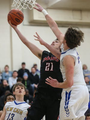 Holy Cross' Tyler Bezold puts in a layup in front of NewCath's Ben Weyer during the first quarter in the Ninth Region All A Classic Championship game at Lloyd, Saturday, January 23, 2016.