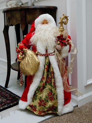 One of many Santa figures stands in the entry way of the Livonia home.