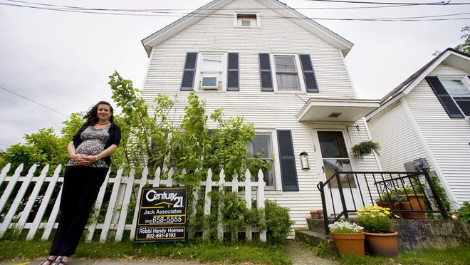 Maura Collins of the Vermont Housing Finance Authority next to a home for sale in Burlington in this file photo from 2011.