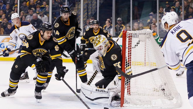 Boston Bruins' Jonas Gustavsson (50) blocks a shot by Buffalo Sabres' Evander Kane (9) during the first period of an NHL hockey game in Boston.