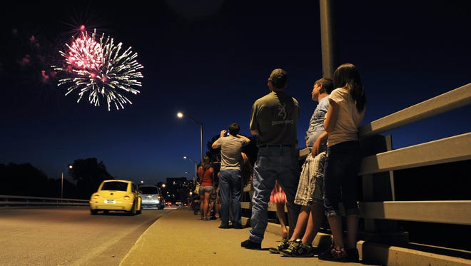 People watch fireworks from the State Street bridge during the Stars and Stripes celebration for the 2011 Fourth of July.