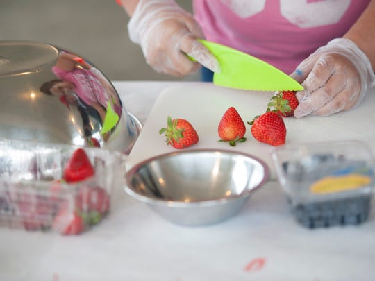 Hannah Williamson cuts up strawberries for her Fruit Bowl Sugary dip creation during the Chef Battle at the Ross County Fair, sponsored by Adena Health System, YMCA of Ross County, and the Chillicothe and Ross County Public Library.  Various fruits and vegetables were provided to illustrate how people should just experiment and try new things instead of eating and cooking the same ways every time.